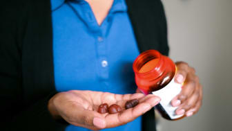 Close-up of unrecognizable woman holding fruit-flavored multivitamins
