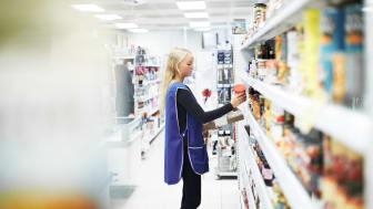 A grocery store employee restocks shelves.
