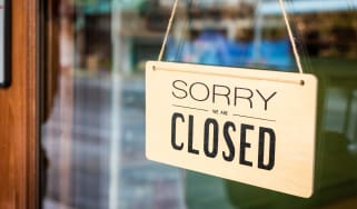 "A ""closed"" sign hangs in a storefront window"