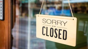 """A """"closed"""" sign hangs in a storefront window"""