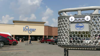 A Kroger-branded shopping cart sits in front of a Kroger grocery store.