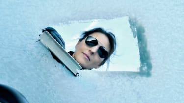 Photo of woman clearing snow from car windshield