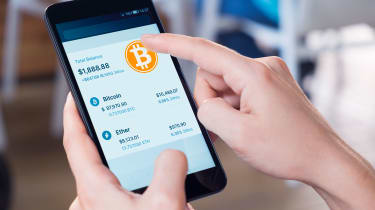 hands holding smartphone. screen has bitcoin position up.
