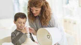 A mother helps her young son change a lightbulb