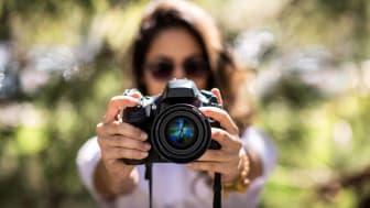 A woman holding a DSLR camera.