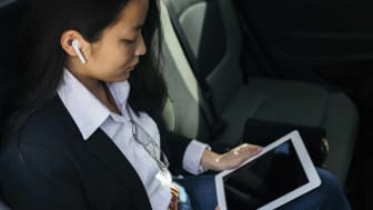 Woman using Apple Airpods and an iPad.