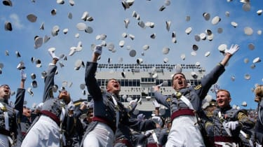 picture of West Point cadets at graduation throwing their hats into the air