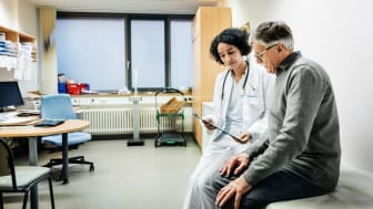 Senior citizen going over medical chart with doctor in exam room