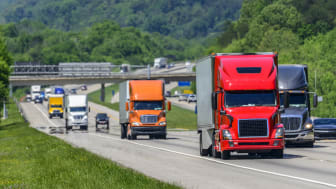 A steady flow of semis lead the way down a busy interstate highway in Tennessee.Heat waves rising from the pavement give a nice shimmering effect to vehicles and forest behind the lead trucks