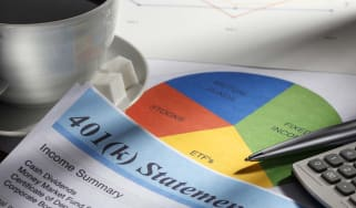 Close up of a 401(k) statement. The statement is surrounded by a cup of coffee, a pie chart of personal finances, a calculator and a pen with a soft focus on a graph in the background.This im