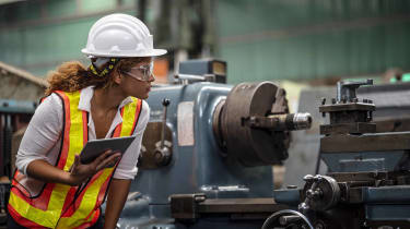 A female factory worker examines a machine