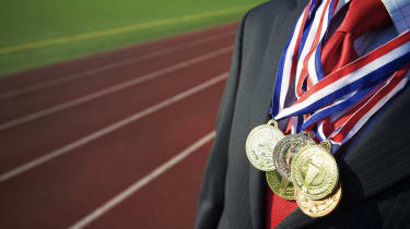 Businessman stands draped with gold, silver, and bronze medals with a running track in the background