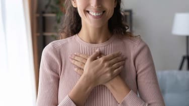 A smiling woman holds her hands on her heart.
