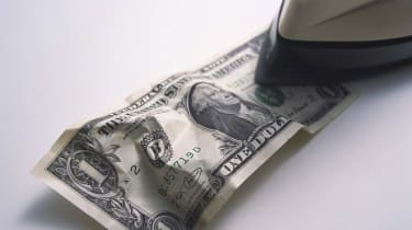 An iron ironing a wrinkled dollar bill