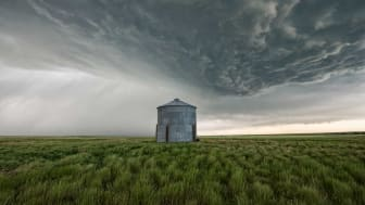 Silo in a field with a huge storm moving in