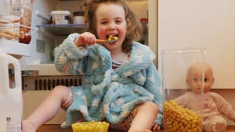 Young girl helping herself to cereal and milk sitting on the floor in front of an open refrigerator