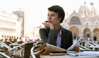 A woman in a business suit sits in a European cafe.