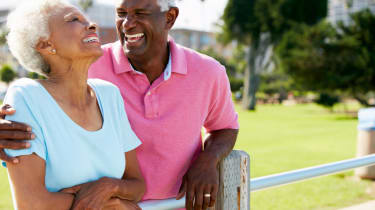 Senior Couple Walking In Park Together Laughing