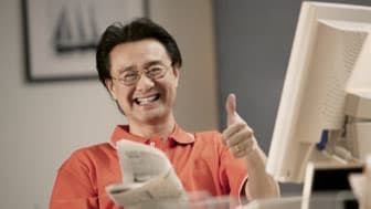 Man at computer holding newspaper