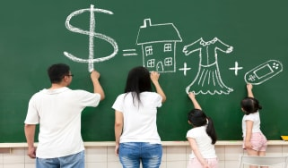 picture of a family drawing a dollar sign, house, clothes, and video game symbol on a chalkboard