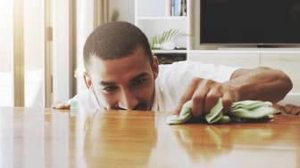 Shot of a focused young man cleaning the surface of a table with cleaning equipment at home during the day