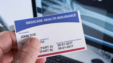 A hand holds a Medicare health insurance card