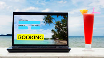 "A laptop with ""booking"" on a screen sits overlooking a resort with a fancy cocktail next to it"