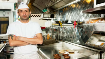 picture of a fry cook standing with arms folded in front of a grill