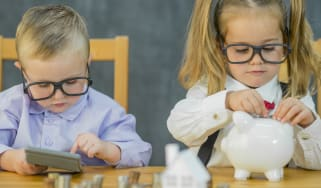 Two toddlers are dressed as adults wearing business attire featuring suspenders and a bow tie. Both of them wear thick rimmed eye glasses and are playing with coins, a piggy bank, money, and
