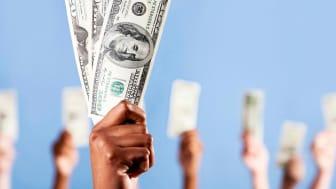 Hands holding one-hundred dollar bills