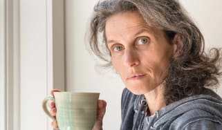 A quizzical-looking woman takes a sip of coffee.