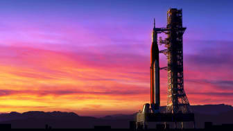 A rocket on a launchpad at sunrise