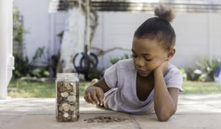 Young african female lying on the floor with a jar filled with coins counting how much she saved.