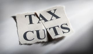 """picture of a piece of paper with """"Tax Cuts"""" written on it that has been cut in half"""