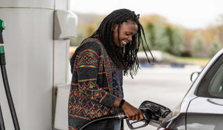 Woman with braids pumping gas
