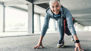 A fit female runner with white hair crouches in the ready position as if poised to start a race.