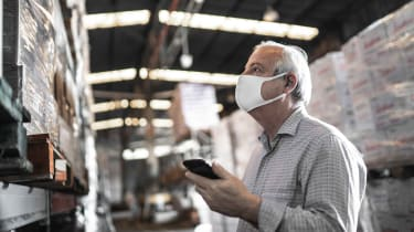 photo of older man with mask working in warehouse