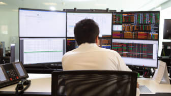 picture of investment fund manager looking at several computer screens