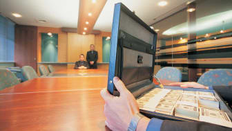 picture of man at long desk with a briefcase full of cash