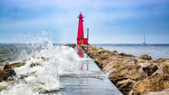 Lake Michigan waves crash over a pier at Muskegon Channel South Pier Lighthouse in Muskegon, Michigan