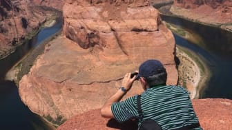 Horsehoe Bend Canyon, a horseshoe-shaped meander of the Colorado River located near the town of Page, Arizona, in the United States. A photographer is lying down taking a picture from the top of the canyon.