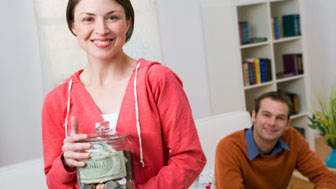 Smiling couple with savings jar