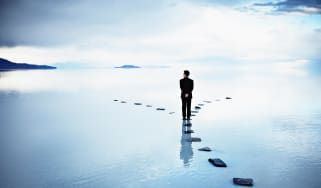 A man stands on a stepping stone where the path diverges ahead.