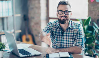 Concept of successful job interview. Portrait of happy cheerful smiling glad worker giving you a hand for handshaking, he is sitting at his comfortable office in front of laptop
