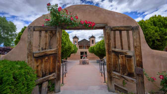 Heavy wooden gates open at the pilgrimage site of El Santuario de Chimayo, a National Historic Landmark in Chimayo, New Mexico