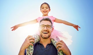 A smiling dad carries his daughter on his shoulders.