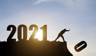 "A man pushing the ""0"" off a cliff to reveal the year 2021."