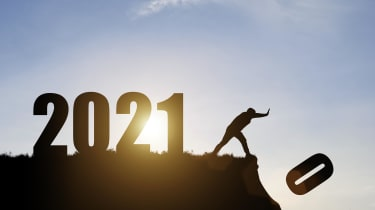 """A man pushing the """"0"""" off a cliff to reveal the year 2021."""