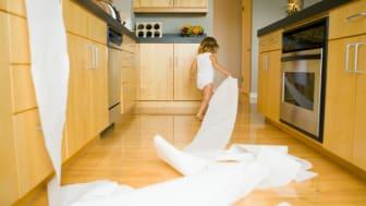 Girl (2-4) spilling roll of paper towels across kitchen floor