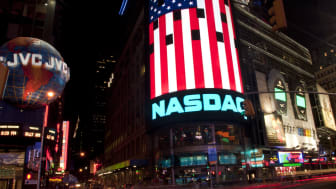 New York, New York -- September 21, 2003: Nasdaq sign with huge American flag in Times Square.